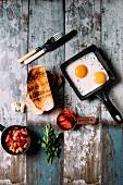 Breakfast with mixed beans, sourdough toast, eggs, chorizo, garlic and flat leaf parsley