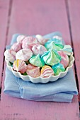 Various coloured meringue kisses in a bowl on a pink wooden background