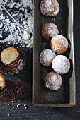 Castagnole (deep fried pastries, Italy) with icing sugar and melted chocolate