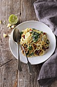 Spaghetti with mashed avocado, dried tomatoes, and kale