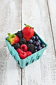 Different fresh berries in a cardboard box