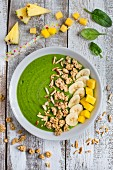 A green smoothie bowl with spinach, mango, pineapple, banana and muesli