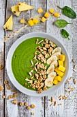 Grüne Smoothie-Bowl mit Spinat, Mango, Ananas, Banane und Müsli