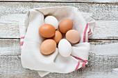 Chicken eggs in a tea towel on a wooden background (seen from above)