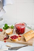 Strawberry jam in a glass jar, and spread on a slice of white bread