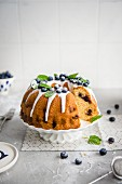 Sponge cake with blueberries and icing, sliced
