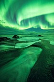 Aurora borealis over coastal rocks
