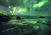 Aurora borealis over coastal rocks