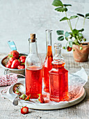 Homemade strawberry vinegar in decorative glass bottles