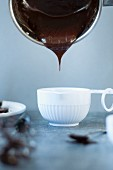 Dark chocolate cream pouring into a small bowl