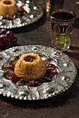 Honey semolina cakes with saffron, dark red grapes and green pistachios