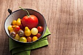 A variety of tomatoes in an antique enamel bowl on wood background with a green napkin