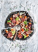 Black pizza with ham, sausage, bacon and vegetables