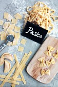 Different varieties of homemade pasta with a small wooden board, a pastry wheel, and a 'Pasta' sign