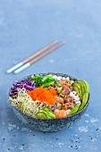 A Poke bowl with wakame seaweed, tuna, sushi rice, salmon, alfalfa sprouts, red cabbage, sesame seeds, cucumber slices, spring onions, avocado, and tobiko