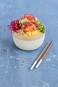 Poke Bowl mit Thunfisch, Lachs, Sushireis, Tobiko, Avocado, Möhren, Mango und Sprossen