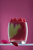 Matcha chia pudding with raspberry puree in a glass