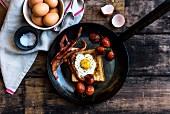 Toast mit Spiegelei, Bacon und Tomaten in der Pfanne (Aufsicht)