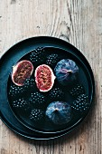 Blackberries and figs on a black plate (top view)