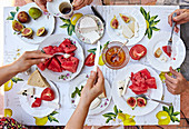 A summer breakfast table with cheese, melon, figs and coffee