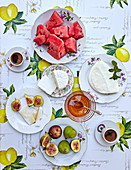 A summer breakfast with cheese, melon, figs and coffee (seen from above)