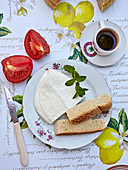 A summer breakfast with halloumi, bread, tomatoes and coffee