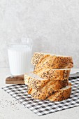 A stack of sliced poppy seed bread with a glass of coconut milk