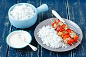 Chicken skewers with cherry tomatoes and pepper served with rice and a yoghurt dip