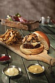 A mushroom cheeseburger with fries on a chopping board