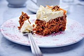 A piece of carrot cake with cream frosting on a plate