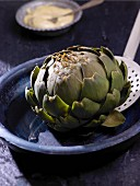 A boiled artichoke on a slotted spoon