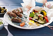 Cevapcici and vegetables wrapped in paper on a plate