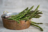 Fresh green asparagus in a metal bowl