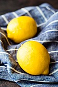 Two lemons on a blue and white striped linen cloth