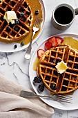 Waffeln mit Beeren, Butter und Ahornsirup zum Kaffee (Aufsicht)
