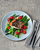 Wild sea bass with asparagus and tomatoes