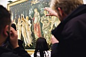 Tourists looking at Botticelli's 'Allegory of Spring' behind glass at the Uffizi Gallery in Florence, Italy