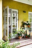 Sommerliche Blumen auf der überdachten Terrasse am Haus