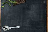 Herbs, a pot holder, and a spatula on a slate board