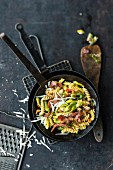 Pasta with leek, bacon and cranberries in a frying pan
