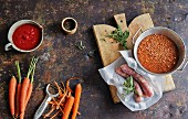 Ingredients for winter soups (carrots, tomatoes, lentils, salsicce)