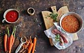 Zutaten für Wintersuppen (Möhren, Tomaten, Linsen, Salsicce)