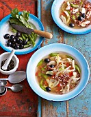 Lemon chicken soup with olives and red rice