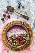 Berry smoothie bowl with hazelnuts, pumpkin seeds and oat flakes
