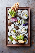 California rolls served on a wooden tray with stones (Japan)