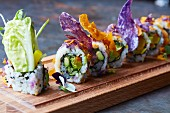 Sushi with vegetables on a wooden plate, decorated with edible flowers(Japan)