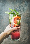 Woman s hand holding glass of blood orange citrus lemonade with mint and ice, dark brown stone background