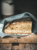Rustic French rye bread loaf covered with kitchen towel over shabby wooden board