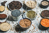 Various raw uncooked grains, beans, cereals in bowls, cups and glass for healthy cooking over marble background