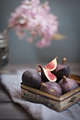 Vintage tin full of fresh figs topped with a quartered fruit